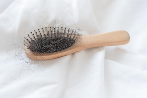Femme regardant ses cheveux pour le problème de perte de cheveux