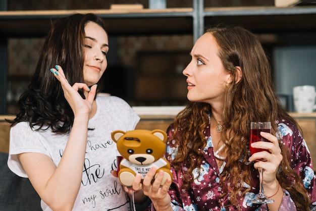 Femme regardant son amie montrant le signe ok