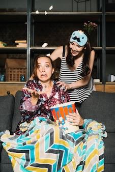 Femme regardant son amie peur assis sur un canapé avec du pop-corn
