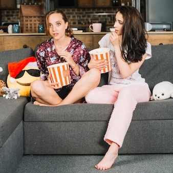 Femme regardant son amie en regardant la télévision