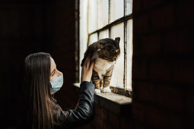 Femme regardant son chat. ils sont debout près d'une fenêtre dans un masque de protection.