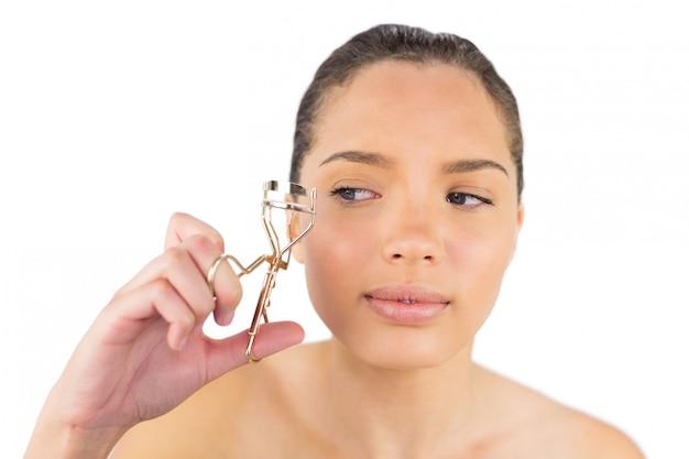 Femme regardant son recourbe-cils