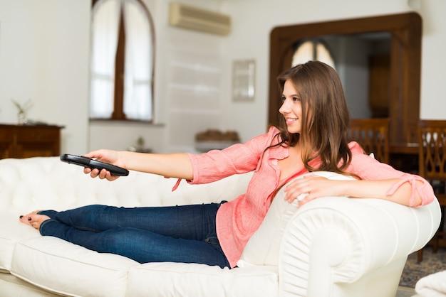 Femme regardant la télévision à la maison