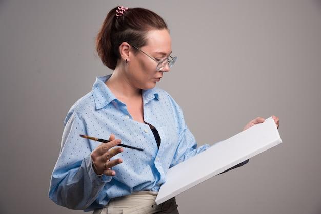 Femme regardant toile vide et pinceau sur fond gris