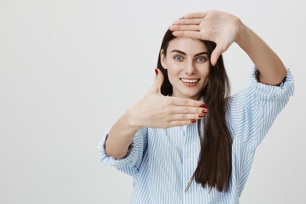 Femme regardant à travers le geste du cadre, souriant comme inspiration de recherche