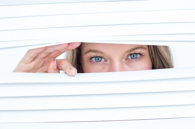 Femme regardant à travers un store
