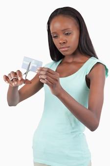 Femme regardant triste détruisant sa carte de crédit