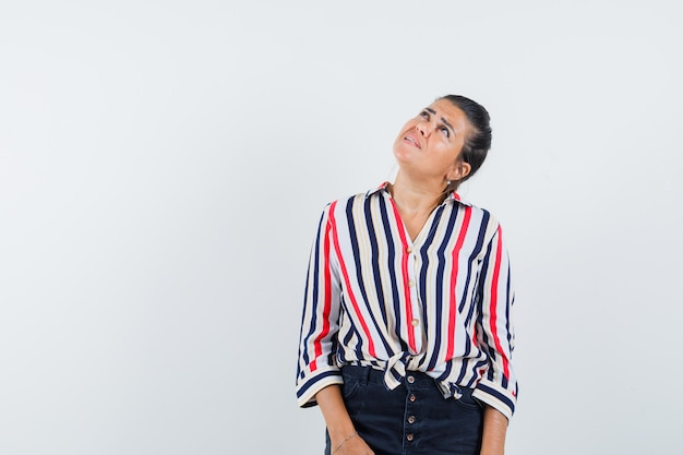 Femme regardant vers le haut en chemise, jupe et à concentré