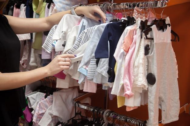 Femme regardant les vêtements de bébé