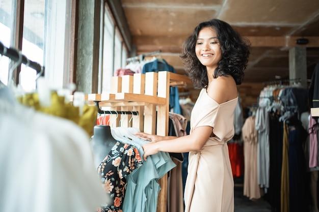 Femme regardant des vêtements dans le magasin de mode