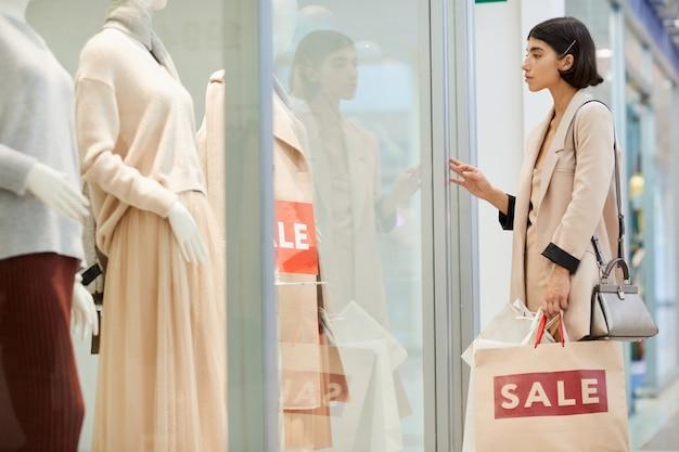 Femme regardant des vitrines dans la boutique