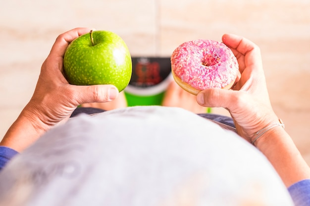 Une femme regarde un beignet et une pomme pour sélectionner son mode de vie nutritionnel - elle est sur une échelle de poids