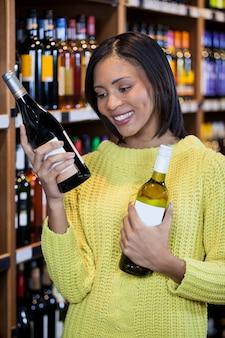 Femme regarde, à, bouteille vin, dans, épicerie, section