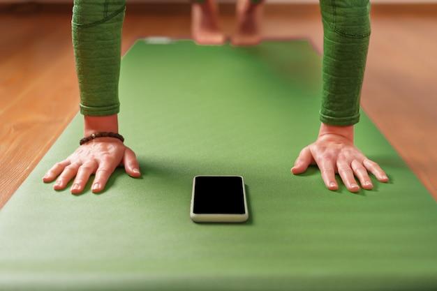 Une femme regarde des cours de yoga sur son smartphone alors qu'elle est assise sur un tapis d'exercice vert. le concept de formation dans le salon de la maison. technologie et sport