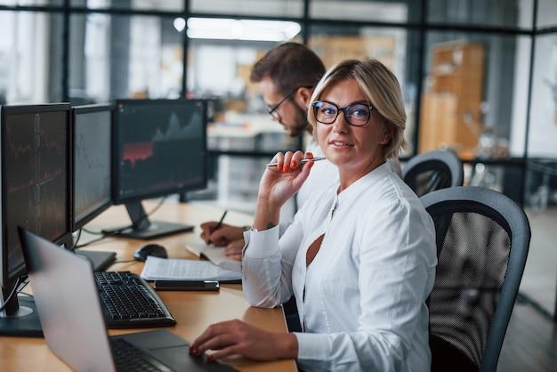 La femme regarde dans la caméra. deux courtiers en vêtements formels travaillent au bureau avec le marché financier.
