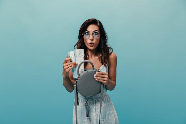 Femme regarde dans la caméra avec surprise et met des billets d'avion dans son sac