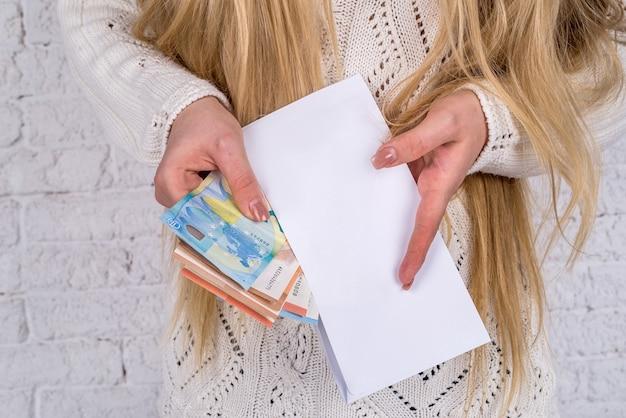 Femme regarde dans l'enveloppe - vérifie le salaire