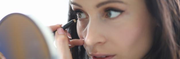 La femme regarde dans le miroir et peint ses yeux