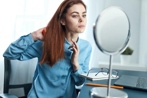 La femme regarde dans la peau propre de matin de cosmétiques de coiffure de miroir
