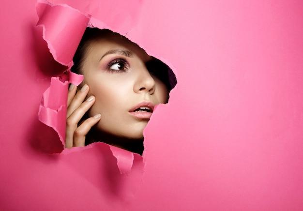 Femme regarde dans le trou couleur papier rose, mode beauté maquillage et cosmétiques, salon de beauté
