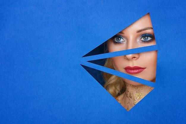 Une femme regarde dans le trou du papier, beau maquillage.
