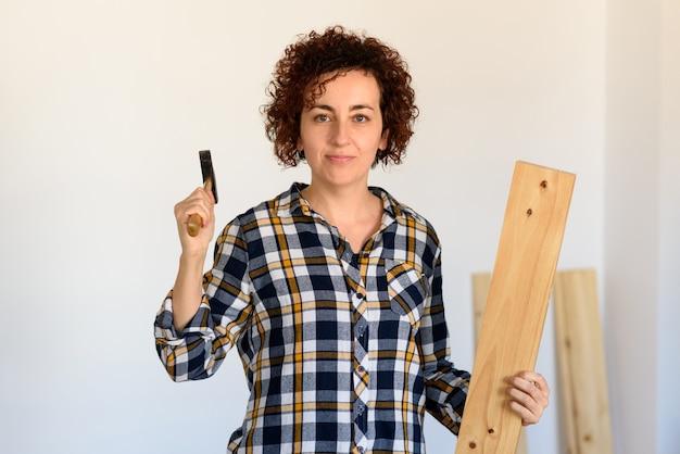 Femme regarde avec défi la caméra tout en tenant un marteau en bois et bricolage