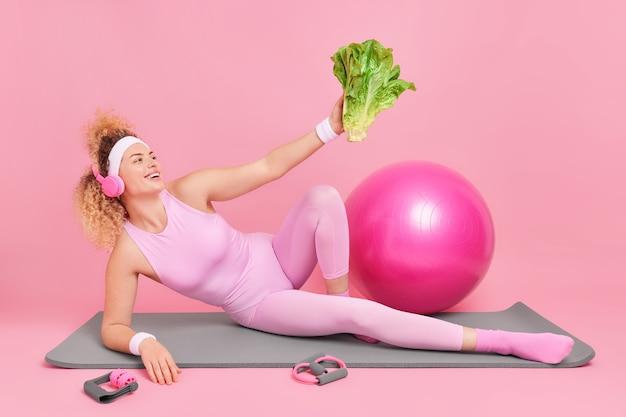 Une femme regarde un légume vert vous motive à mener une vie saine vêtue de vêtements de sport allongée sur un tapis de fitness écoute de la musique via un casque fait une pause après une longue séance d'entraînement