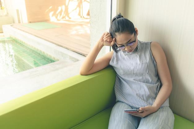 Femme regarde son smartphone sur le canapé près de la fenêtre.