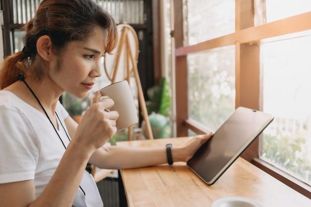 La femme regarde la tablette et boit du café dans le café