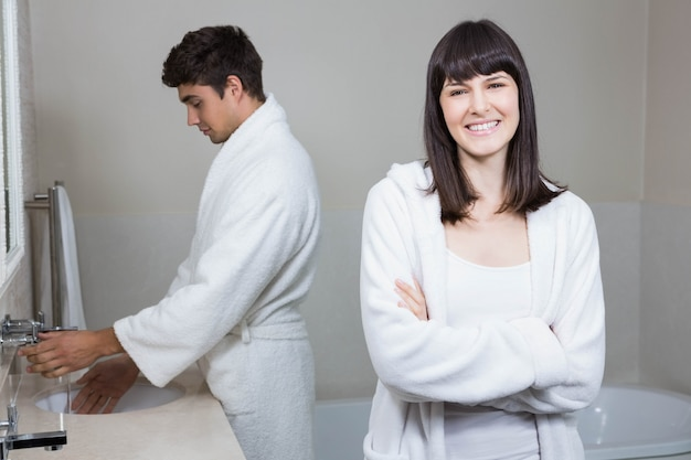 Femme, regarder appareil-photo, et, homme, debout, près, lavabo