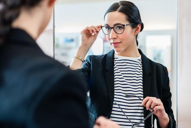 Femme, regarder, lunettes, miroir, opticien