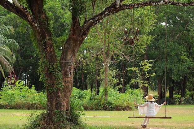Femme relâche, sur, balançoire bois, sous, les, grand arbre, dans parc