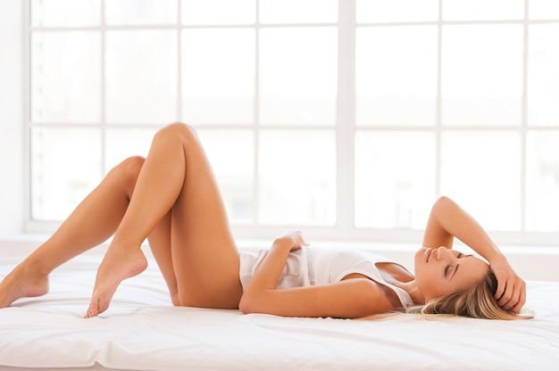 Femme relaxante au lit. belle jeune femme en maillot allongé sur le lit et gardant les yeux fermés