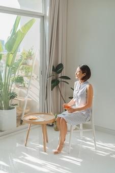 Femme relaxante et lisant un livre près de la fenêtre dans le salon