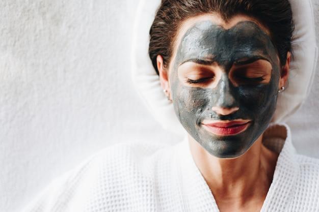 Femme relaxante avec un masque facial au charbon de bois