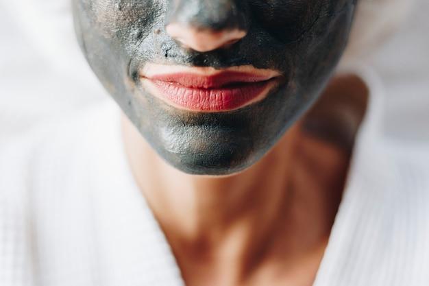 Femme relaxante avec un masque facial au charbon