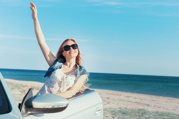 Femme relaxante sur la plage en voiture