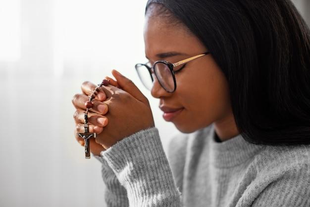 Femme religieuse tenant des perles de chapelet