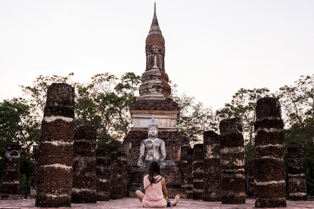 Femme religieuse visitant les vestiges du parc national de sukhothai, l'ancienne ville au patrimoine bouddhiste en thaïlande.
