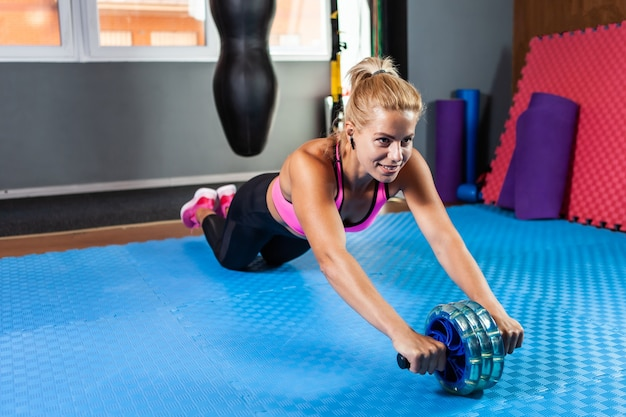 Femme de remise en forme active et forte pratiquant des exercices abdominaux à rouleaux ab en cours de remise en forme. concept minceur, mode de vie sain
