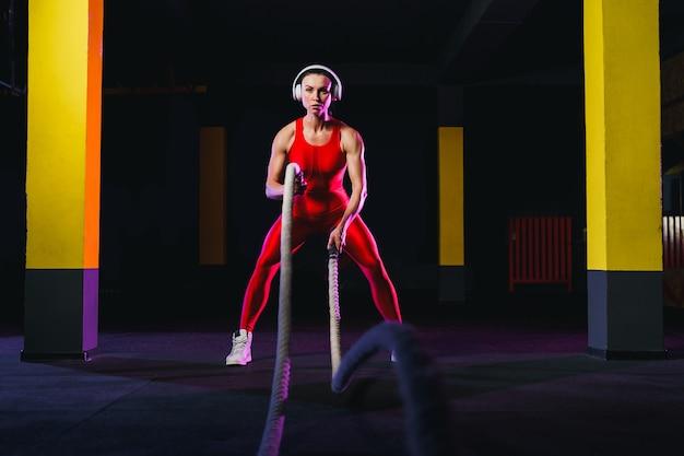 Femme de remise en forme à l'aide de cordes d'entraînement pour faire de l'exercice au gymnase. athlète travaillant avec des cordes de combat au cross gym.