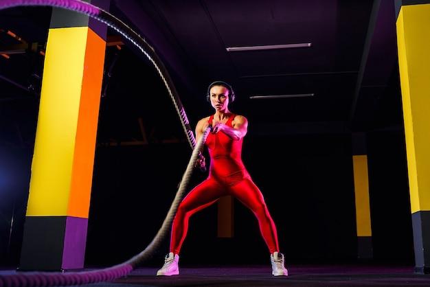 Femme de remise en forme à l'aide de cordes d'entraînement pour faire de l'exercice au gymnase. athlète travaillant avec des cordes de combat au gymnase.