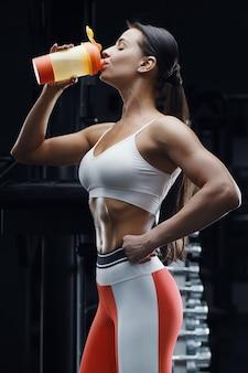 Femme de remise en forme athlétique buvant de l'eau de shaker orange à l'entraînement dans la salle de gym. fille athlétique assez caucasienne. concept de remise en forme et de sport.
