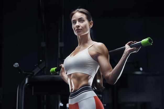 Femme de remise en forme athlétique à l'entraînement en salle de gym avec barre de corps étirant les muscles concept de remise en forme et de sport. bodybuilder caucasien faisant des exercices d'abs dans la salle de gym