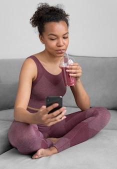 Femme de remise en forme ayant un jus de désintoxication tout en utilisant un smartphone