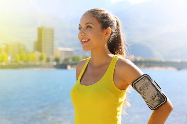 Femme de remise en forme avec brassard pour la technologie du téléphone faisant du jogging exercice marathon qui s'étend au chaud le matin dans le lac de la ville.