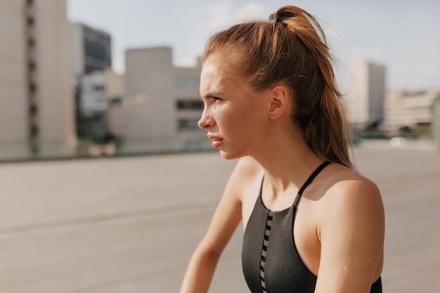 Femme de remise en forme confiante qui s'étend sur un rail à l'extérieur en journée ensoleillée sur la place du sport