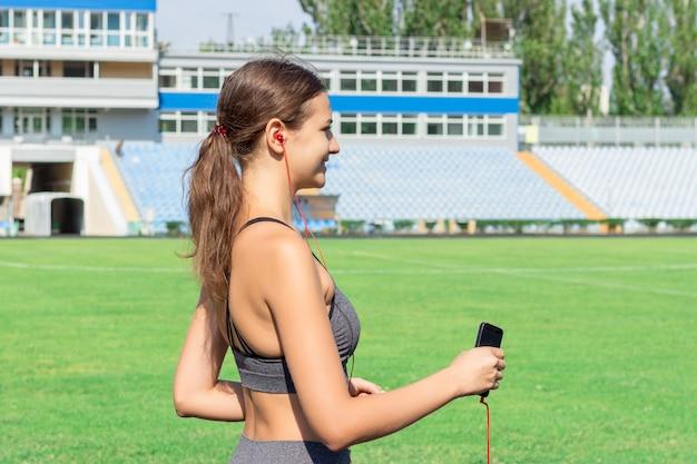 Femme de remise en forme dans la musique d'écoute de sportswear et en cours d'exécution sur le stade de football.