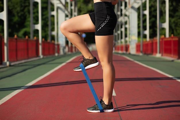 Femme de remise en forme faisant des étirements des jambes avec la bande de résistance en caoutchouc sur le pont. espace pour le texte