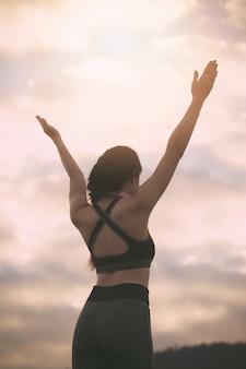 Femme de remise en forme faisant de l'exercice au coucher du soleil,